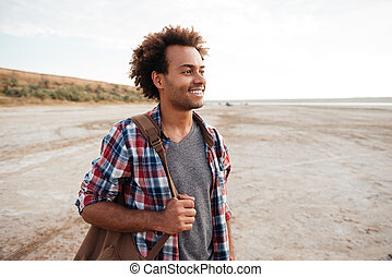 Happy curly african young man with backpack on the beach