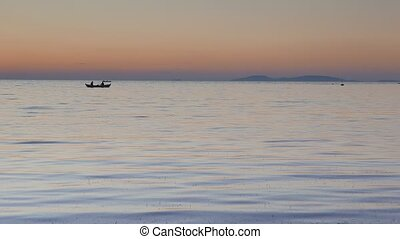 Calm sea with a silhouetted rowing boat at sunset. 4k