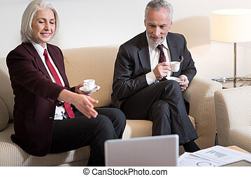 Happy businesswoman drinking coffee with her colleague