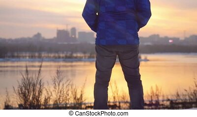 Yang man standing outdoor and looking on sunset in the urban...