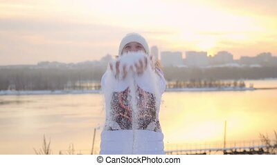 Happy attractive woman having fun and throwing snow in winter field on sunset city background in slowmotion.