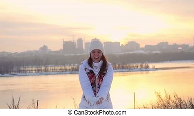Beautiful woman having fun with snow during a cold winter day in slowmotion. 1920x1080