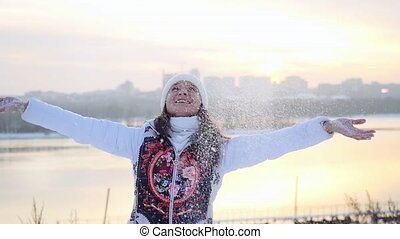 Happy young active woman having fun and throwing snow in winter field on sunset city background in slowmotion. 1920x1080