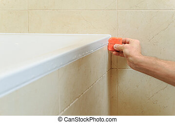 Worker puts silicone sealant.