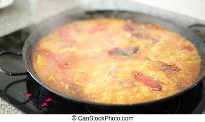 Paella cooking on an electric stove.