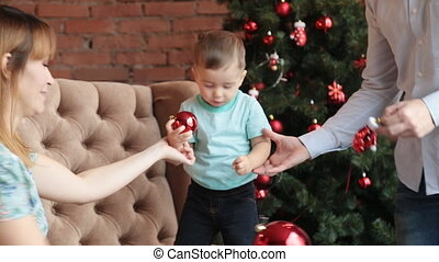 happy family sitting by the christmas tree - happy family...
