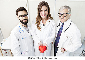 group of doctors with a symbol heart in their hands