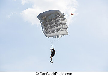Parachutist with parachute is flying in the blue sky -...