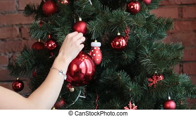 Smiling woman decorating Christmas tree at home and...