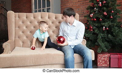 Father and son near christmas tree - Son adjusting star on...