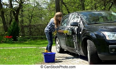 Female washing her car at house yard in garden. Woman with...