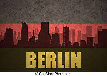 abstract silhouette of the city with text Berlin at the vintage german flag