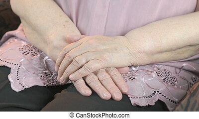 Man strokes the old woman's hands during illness