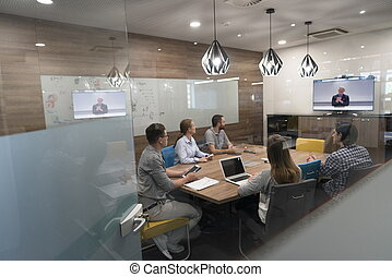 start up business people group attending videoconference...