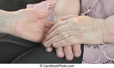 Woman strokes old woman's hands in times of stress - Woman...