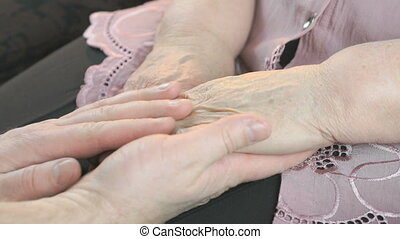 Man strokes old woman's hands in times of stress - Man...
