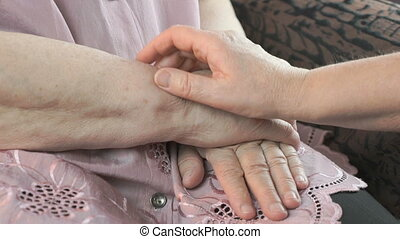 Woman holding flabby wrinkled hands of aged woman