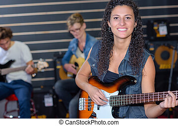 happy girl playing an acoustic guitar in a band