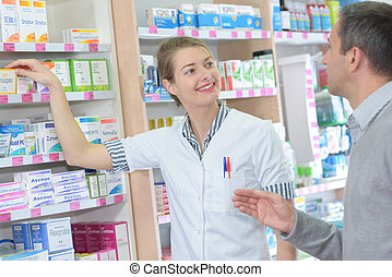 professional pharmacist helping a customer