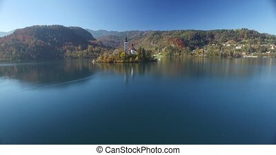 Aerial view of St Martin church on island and Bled lake landscape with mountain