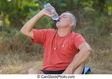 man drinking water bottle in a park