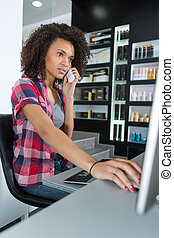 woman checking disponibility in computer for phone appointment