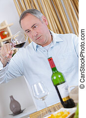 middle-age man tasting wine