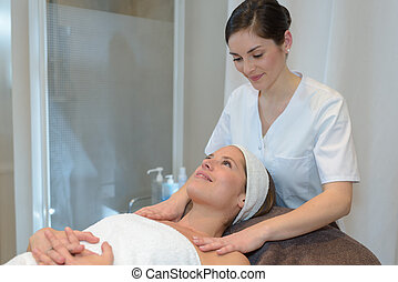 young woman lying and having face massage in spa