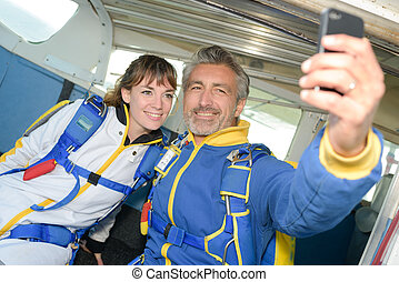 smiling people ready to jump from an airplane