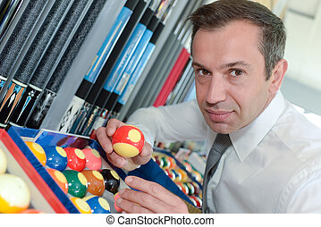 serious man prepares balls for start of game billiard