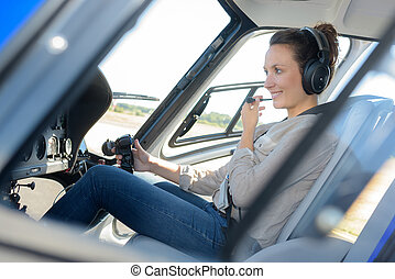 portrait of young beautiful woman pilot in a airplane