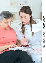 nurse in home visit helping old woman following treatment