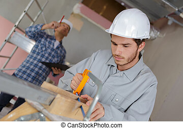 young man cutting a board with a hand saw