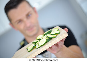 man showing sliced cucumber laying on a wooden chopping...