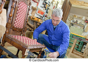 old craftsman repairing a chair in his workshop