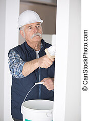 senior man painting a wall at construction site