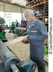 metallurgy manufacture older worker concentrated on machine