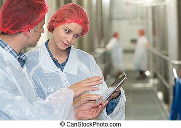 factory workers in workshop using digital tablet