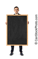 Businessman in suit standing and holding blackboard in...