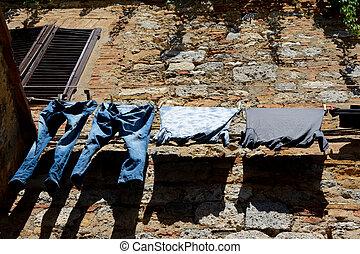 Clothes hanging at brick and stone wall