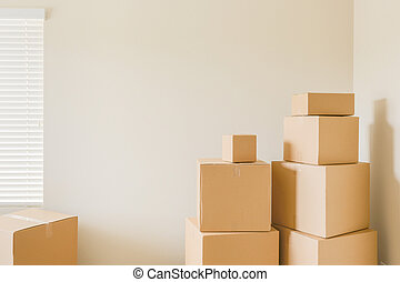 Variety of Packed Moving Boxes In Empty Room