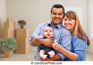 Mixed Race Family with Baby in Room with Packed Moving Boxes