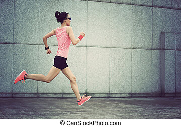 young fitness sport woman running against wall on city