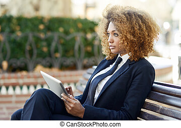 Black woman using tablet computer in town - Beautiful black...