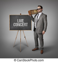 Live concert text on blackboard with businessman holding...