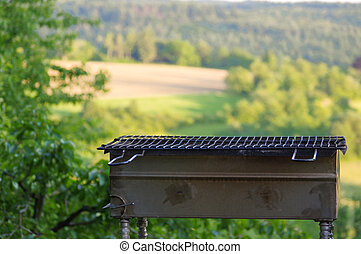 Empty portable BBQ grill in front of a fresh green summer...