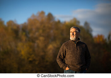 Portrait of a senior man outdoors, walking in a park...