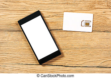 Smartphone and SIM card on office table, top view -...