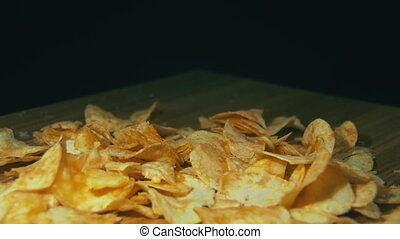Potato Chips are Falling on a Wooden Table on Black...