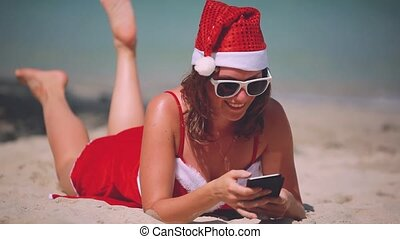 Christmas young smiling woman in red santa hat taking...